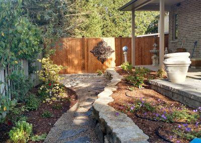 Stone pathway, raised flower bed, and stone patio