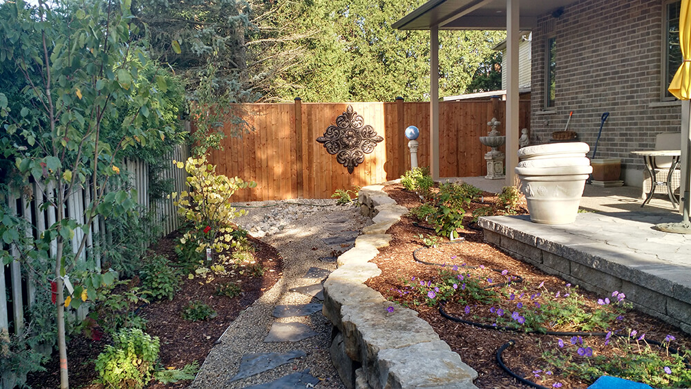 Raised flower bed with perennial flowers, shrubs and trees