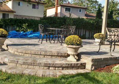 Hardscaping - round stairs lead to raised patio with multiple sitting areas