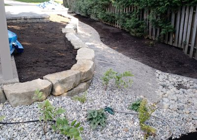 Added raised flower bed with armour stone retaining wall alongside stone pathway