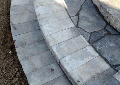 Hardscaping - rounded stone stairs lead to private raised stone patio