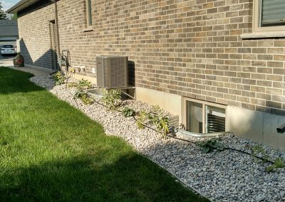 Side landscaped flower bed covered with stone to reduce maintenance