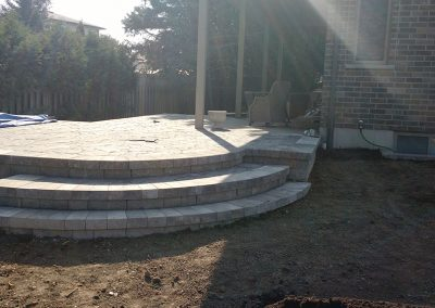 Raised stone patio with rounded stairs built into sloped grade