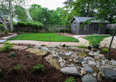 Pondless stream using natural river rock by A Touch of Dutch Landscaping