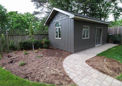 Interlocking brick path leading through perennial beds to garden shed