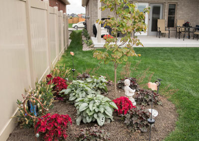 Backyard flower bed with a mix of perennial and annual plants